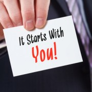 A businessman holding a business card with the words, It starts with You.